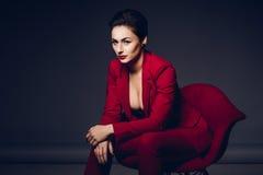 可爱的女商人 一个性感的年轻企业夫人的画象一套红色衣服的在黑暗的背景 免版税库存图片