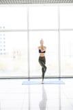 年轻可爱的女子实践的瑜伽,常设瑜伽锻炼,在地板窗口附近的佩带的运动服有城市视图 库存照片