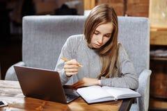可爱的女学生为学会新的信息的考试做准备 考虑在膝上型计算机的新的电影的有天才的作家 库存图片