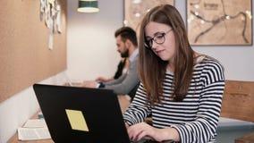 年轻可爱的女孩与膝上型计算机一起使用在一个现代起始的办公室 库存图片