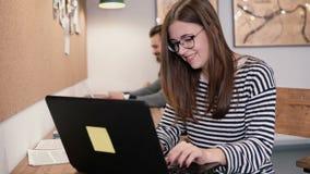 年轻可爱的女孩与膝上型计算机一起使用在一个现代起始的办公室 免版税库存图片