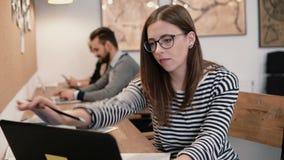 年轻可爱的女孩与膝上型计算机一起使用在一个现代起始的办公室 库存照片