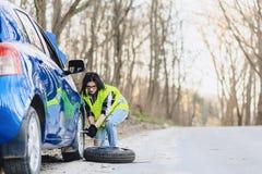 可爱的女孩从汽车去除轮子在单独路 免版税库存照片