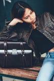 年轻可爱的女孩凉快的时尚样式皮夹克和皮包的在她旁边 免版税库存照片