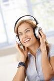 可爱的女孩听的音乐微笑 免版税库存图片