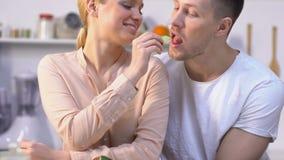 可爱的女孩哺养的心爱的男朋友菜,愉快的夫妇在厨房里 股票视频