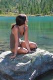 可爱的女孩在一块石头摆在高山湖 免版税图库摄影