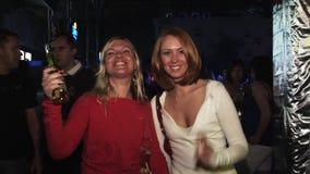 可爱的女孩在党的照相机摆在夜总会 微笑 瓶啤酒在手上 招待 股票录像