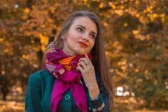 可爱的女孩在有一条桃红色围巾的公园站立在她的脖子上并且看  免版税库存照片
