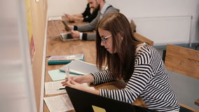 年轻可爱的女孩在现代起始的办公室使用一台膝上型计算机,与文件一起使用,做笔记 股票录像