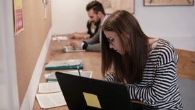 年轻可爱的女孩在现代起始的办公室使用一台膝上型计算机,与文件一起使用,做笔记 影视素材