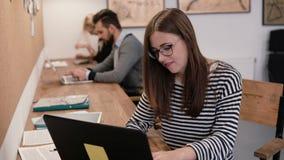年轻可爱的女孩在现代起始的办公室使用一台膝上型计算机,与文件一起使用,做笔记 图库摄影