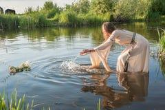可爱的女孩在水中降低花圈 免版税图库摄影