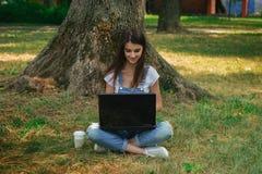可爱的女孩坐草在树和使用下lapto 库存照片
