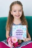 可爱的女孩坐长沙发,拿着桃红色大丁草和母亲` s天卡片花束  日愉快的母亲s 免版税库存照片