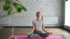 可爱的女孩实践弯曲的瑜伽支持与然后放松在单独会议的容易的莲花姿势的胳膊  影视素材