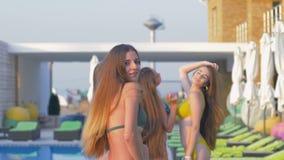 可爱的女孩快乐的公司到游泳衣里获得乐趣在游泳池附近在昂贵的手段在周末期间 影视素材