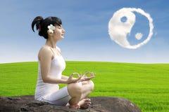 可爱的女孩思考瑜伽在ying杨云彩下 免版税库存照片