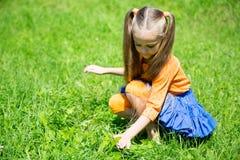 可爱的女孩捉住在草的一只蚂蚱 库存图片