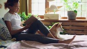 可爱的女孩是阅读书和抚摸在家说谎在床上的美丽的狗在它的所有者附近 现代内部与 影视素材