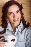 可爱的女孩用在她的胳膊的一只兔子 免版税库存照片