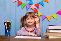 可爱的女孩画象在教室 坐在书桌和学习的小女小学生 免版税库存照片