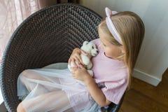 可爱的女孩画象有被充塞的玩具熊的在摆在为摄影的手上,当坐椅子时 库存照片