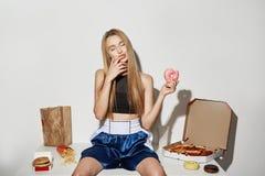 可爱的女孩画象有金发的在体育上面和短裤坐与大相当数量的桌不健康的食物 免版税库存照片