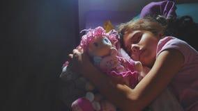 可爱的女孩睡眠在沙发床上和拥抱她的娃娃 睡觉在晚上的小深色的女孩在床上 股票视频