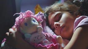 可爱的女孩睡眠在沙发床上和拥抱她的娃娃 睡觉在晚上的小深色的女孩在床上 股票录像