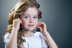 可爱的女孩试穿樱桃作为耳环 免版税库存照片
