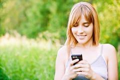 可爱的女孩读sms 免版税图库摄影