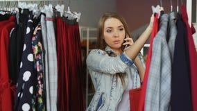 可爱的女孩选择衣裳在现代商店和谈话在手机 五颜六色的裙子特写镜头射击和 股票视频