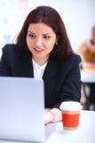 可爱的女实业家坐书桌在有咖啡的办公室 免版税库存图片