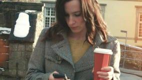 可爱的女实业家室外与手机和咖啡 影视素材