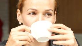 可爱的女实业家饮用的咖啡和放松在夏天大阳台的室外咖啡馆 慢的行动 股票视频