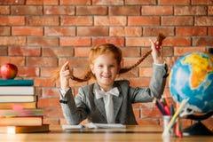 可爱的女小学生在桌上,正面图 库存图片