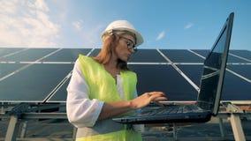 可爱的女性专家在一个巨型的太阳能电池前面站立并且操作膝上型计算机 股票视频