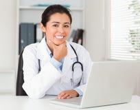 可爱的女性医生与她的膝上型计算机一起使用 免版税图库摄影