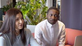 可爱的女性和非洲人坐在非正式会议上在餐馆 股票录像