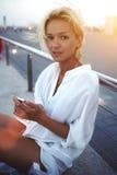 年轻可爱的女性固定的单元电话在手上在休闲时间在温暖的天外面 库存图片