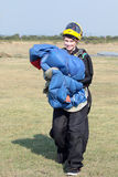 可爱的女性天空潜水者摆在与明亮的蓝色的降伞 免版税库存照片