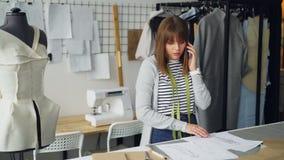 可爱的女性裁缝为她在手机的新的衣裳收藏指令织品并且看剪影 影视素材
