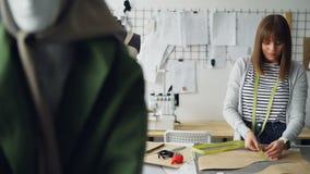 可爱的女性裁缝在她轻的裁缝` s商店测量与卷尺的衣物样式 每天工作 股票录像