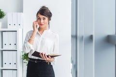 可爱的女性雇员说在电话里,有交涉,使用机动性和片剂在办公室 图库摄影