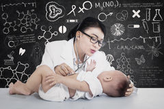 可爱的女性医生核对婴孩在实验室 库存照片