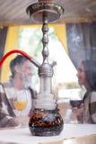 可爱的女朋友和男朋友有水烟筒的 库存照片