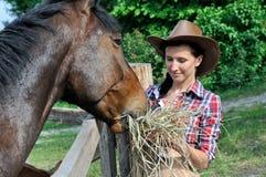 年轻可爱的女牛仔在农场喂养马 免版税库存图片