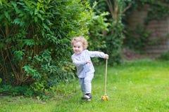 可爱的女婴在有木玩具的庭院里 免版税库存照片