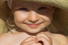 女婴面孔被日光照射了下面帽子 库存图片